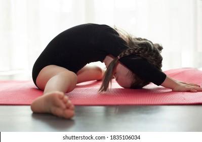 Little girl doing gymnastic exercise. Girl doing yoga at home