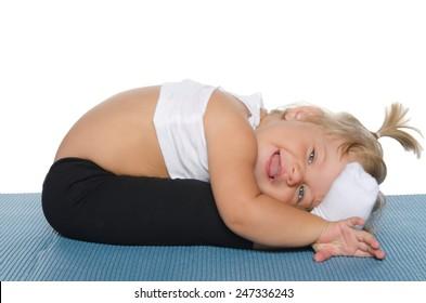 Little girl doing gymnastics on blue mat