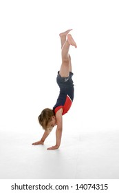 little girl doing a handstand on a white background
