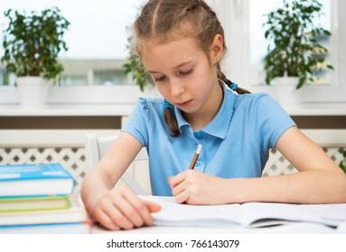Little girl doing her homework at home.