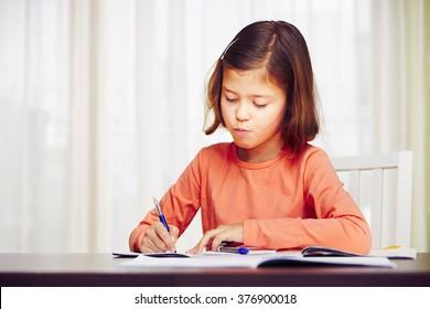 Little girl is doing his homework for elementary school.