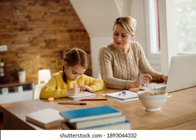 Little girl doing homework while mother is using computer and working at home.