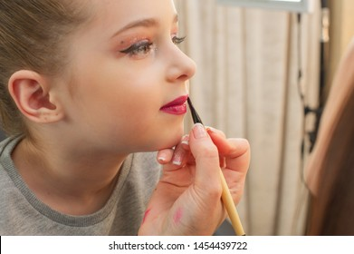 a little girl doing makeup before performing on stage. Preparation before the performance in the dressing room. Makeup artist makes the child makeup in the beauty salon. Hair stylist does her hair.