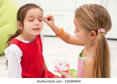 Little girl doing makeup to her girlfriend