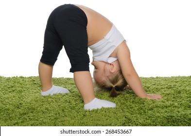 Little girl doing stretching exercises on green carpet