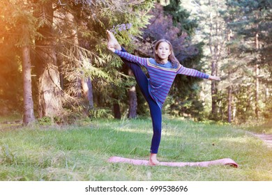 Little girl doing stretching in the forest in the morning. People having fun outdoors. Concept of friendly family and of summer vacation.