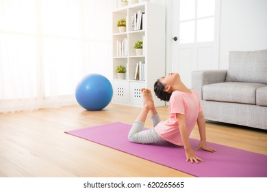 little girl doing yoga exercise on wooden floor with mat legs and body bending in fitness studio near sofa with big windows on background in the living room at home.