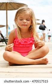 Little girl doing yoga on the beach.