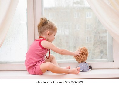 Little girl with doll looking out the window of the house
