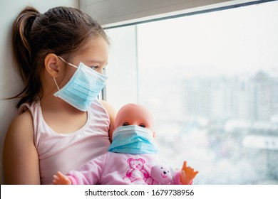 Little girl with doll wearing a protective mask. Copy space. Sadness kid at home in isolation. Sick child Little girls look at the window with longing on the street .