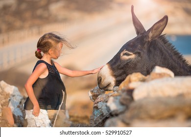 Little girl with donkey on the island of Mykonos