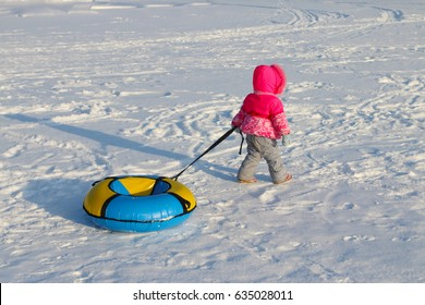 Little girl drags bright snowtube on snow at winter day, back view