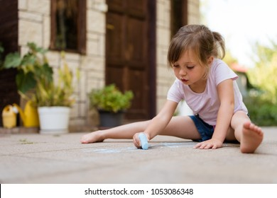 Little girl drawing with chalk on paving in backyard on summer day