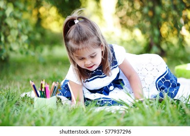 Little girl drawing with colored pencils lying on the grass in the park