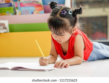 Little girl drawing with colorful crayons and smiling, in colorful room.