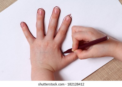 Little girl is drawing contour of the hand.