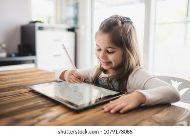 Little Girl Drawing Digital Picture On Electronic Touch Tablet With Stylus Pen