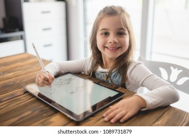 Little Girl Drawing Digital Picture On Tablet Using Stylus Pen