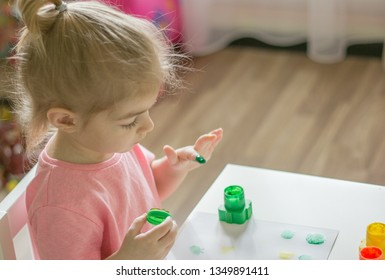 little girl drawing with fingerpaints , dunks his finger in the paints, color finger stamps.