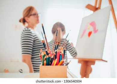 Little girl drawing with her mother at home. Closeup of pencils and brushes.