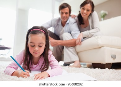 Little girl drawing with her parents in the background while lying on a carpet