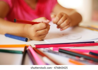 Little girl drawing at home. Focus is on hands. Colorful image.