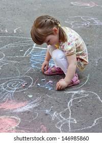 little girl drawing on asphalt