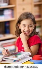 kleines Mädchen, das ihr Buch anzieht und Spaß am Spieltisch hat