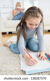 Little girl drawing on paper sitting on floor with mother reading newspaper on the couch