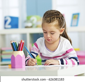 Little girl drawing on a paper.