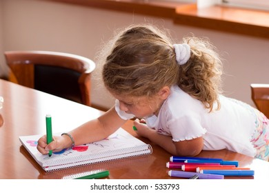 little girl drawing on the table