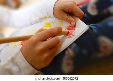 Little girl drawing a picture of her family for her Mum on Mother's Day. Including a red heart expressing the child's love, child's hands, sketch book & pencil/pen