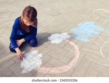Little girl drawing a rainbow with chalk on paving