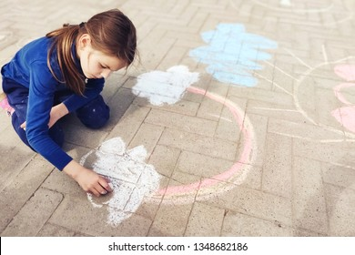 Little girl drawing a rainbow with chalk on paving .