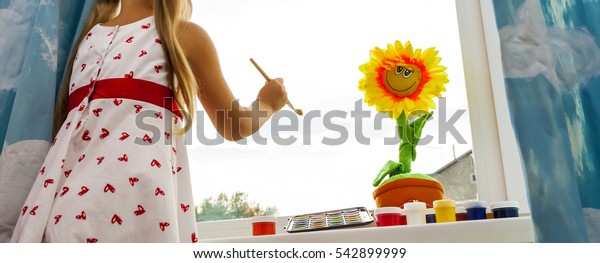 little girl draws a brush on the window