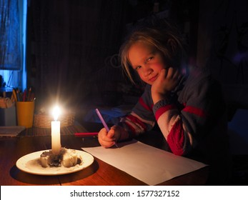 little girl draws by candlelight. The absence of electricity, the living conditions of the child