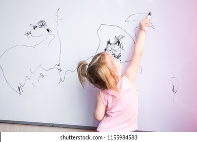 Little girl draws family with marker on a white board