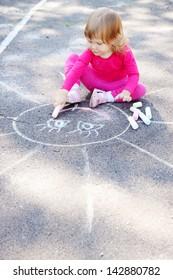 Little girl draws a large sun on asphalt