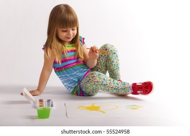 A little girl draws a painting