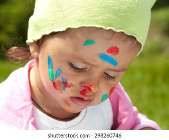 Little girl draws paints on a green lawn