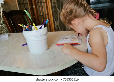 Little girl draws a picture with pencils on a table