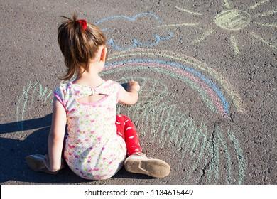 Little girl draws a rainbow with chalk on the asphalt. Child drawings paintings on asphalt concept.