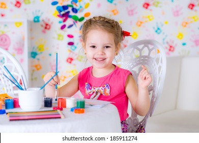 Little girl draws sitting at table in room on bright wall background