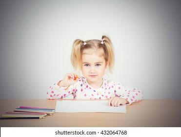 Little girl draws at table pencils. Preschool education.