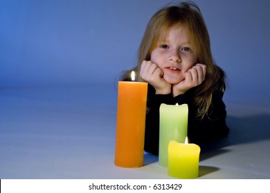 Little girl dreaming by candles