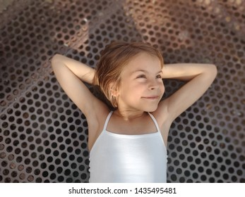 The little girl dreams and lying down and throwing her arms back.