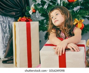 Little girl dreams near a Christmas tree holding a big gift box.