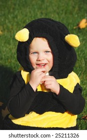 Little girl dress as bee sitting on the grass with sweets.