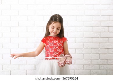Little girl in dress on a white brick wall background