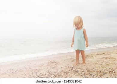 Little girl dressed in blue shirts is walking on the beach.